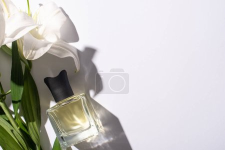 top view of home perfume in bottle near lilies on white background