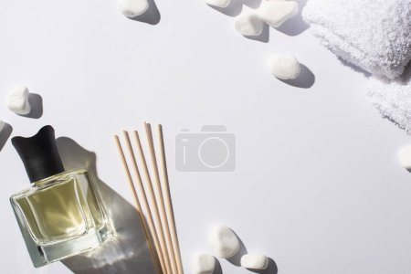 Photo for Top view of aroma sticks with perfume in bottle near spa stones and towel on white background - Royalty Free Image