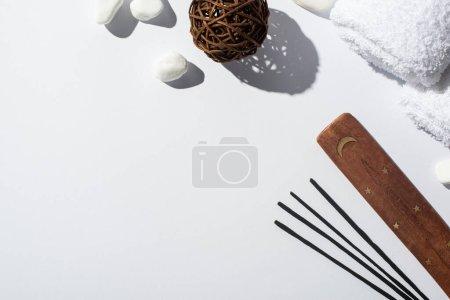 Photo pour Vue de dessus des bâtons d'arôme, support en bois, pierres, serviettes en coton et boule décorative sur fond blanc - image libre de droit