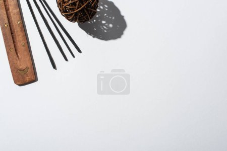 top view of aroma sticks, wooden stand and decorative ball on white background