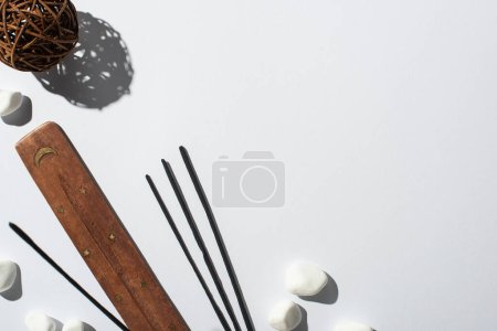 Photo pour Vue de dessus des bâtons d'arôme, des pierres, du support en bois et de la boule décorative sur fond blanc - image libre de droit