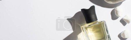 top view of perfume in bottle near stones on white background, panoramic shot
