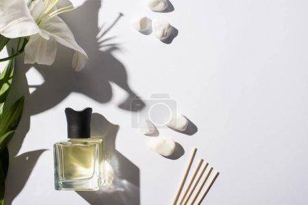 Photo pour Vue de dessus des bâtons d'arôme avec parfum en bouteille près de pierres et fleur de lis sur fond blanc - image libre de droit