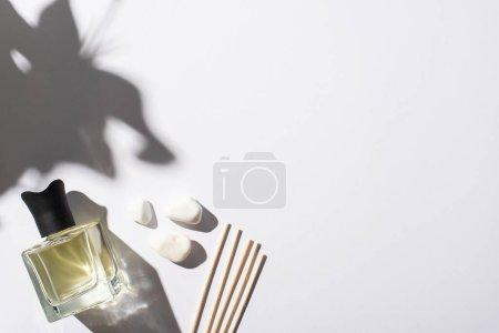 Photo pour Vue de dessus des bâtons d'arôme avec parfum en bouteille près de pierres sur fond blanc - image libre de droit