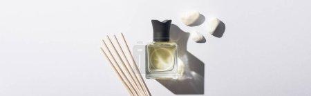 Photo pour Vue de dessus des bâtons d'arôme avec parfum en bouteille près de pierres sur fond blanc, vue panoramique - image libre de droit