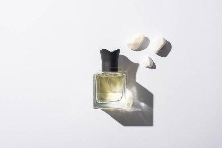Draufsicht auf Parfüm in der Flasche in der Nähe von Steinen auf weißem Hintergrund