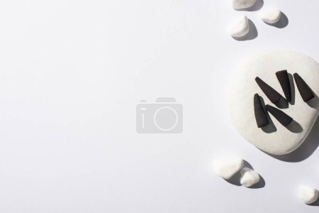 top view of black incense cones, stones on white background