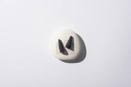 Photo pour Vue de dessus des cônes d'encens noirs sur pierre de spa sur fond blanc - image libre de droit
