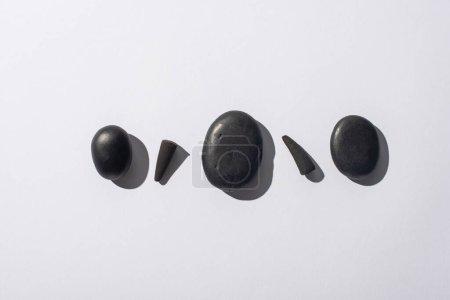 Photo pour Vue de dessus des cônes d'encens noirs et des pierres de spa sur fond blanc - image libre de droit