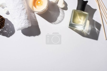 Photo for Top view of aroma sticks with perfume in bottle near cotton towel, stones and candle on white background - Royalty Free Image