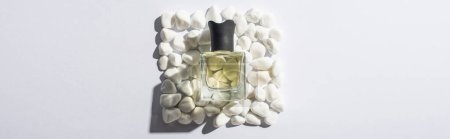 Photo for Top view of home perfume in bottle on square made of stones on white background, panoramic shot - Royalty Free Image