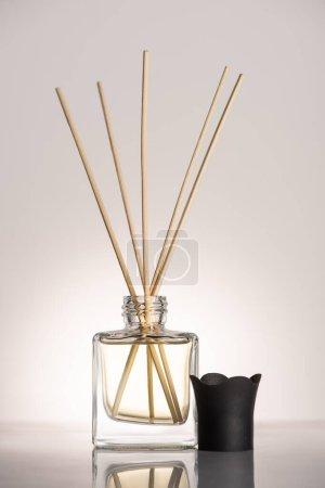 Photo pour Bâtons en bois dans le parfum en bouteille sur fond beige - image libre de droit