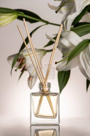 Photo pour Foyer sélectif de bâtons en bois dans le parfum en bouteille près de fleurs de lis sur fond beige - image libre de droit
