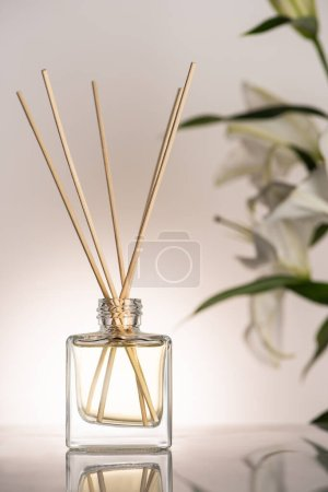 selective focus of wooden sticks in perfume in bottle near lily flowers on beige background