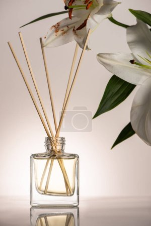 wooden sticks in perfume in bottle near lily flowers on beige background