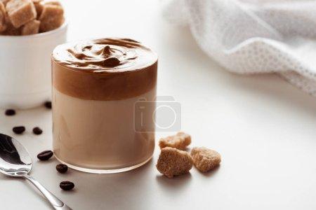 selektiver Fokus von köstlichem Dalgona-Kaffee im Glas in der Nähe von Serviette, Löffel, Kaffeebohnen und braunem Zucker auf weißem Hintergrund