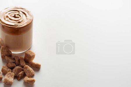 köstlicher Dalgona-Kaffee im Glas in der Nähe von braunem Zucker auf weißem Hintergrund