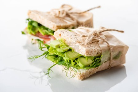 Photo for Selective focus of fresh green sandwiches with avocado on marble white surface - Royalty Free Image