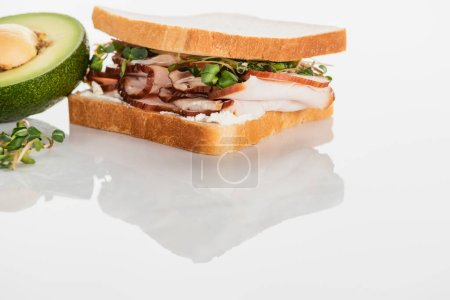 Photo for Fresh delicious sandwich with meat and sprouts on white surface near avocado - Royalty Free Image