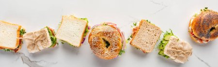 flat lay with fresh sandwiches and bagels on marble white surface, panoramic shot