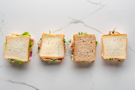 top view of fresh sandwiches on marble white surface