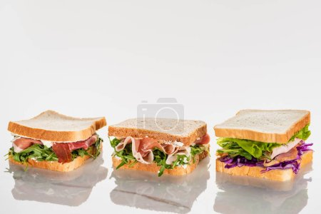 fresh green sandwiches with avocado and jamon on marble white surface