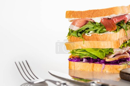 selective focus of fresh sandwiches with meat near cutlery on white surface