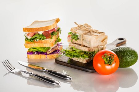 Photo for Fresh sandwiches on wooden cutting board near cutlery and avocado, tomato on white surface - Royalty Free Image