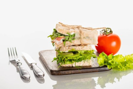 fresh green sandwiches on wooden cutting board near cutlery and tomato on white surface