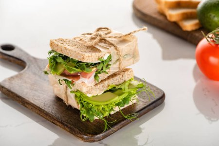 selective focus of fresh green sandwiches with avocado and meat on wooden cutting board on white marble surface
