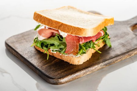 selective focus of fresh green sandwich with arugula and prosciutto on wooden cutting board on white marble surface
