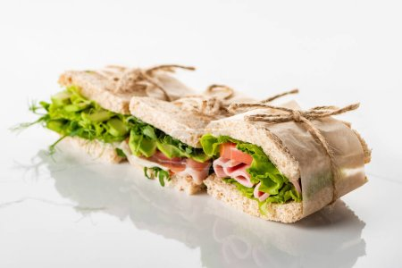 Photo for Selective focus of fresh green sandwiches with avocado and meat on white surface - Royalty Free Image