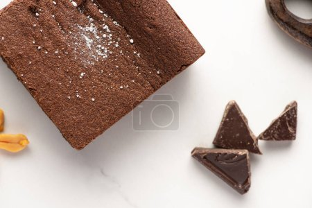 Photo for Top view of delicious brownie piece near chocolate on white background - Royalty Free Image