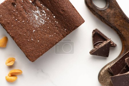 Photo for Top view of delicious brownie piece near wooden cutting board, nuts and chocolate on white background - Royalty Free Image