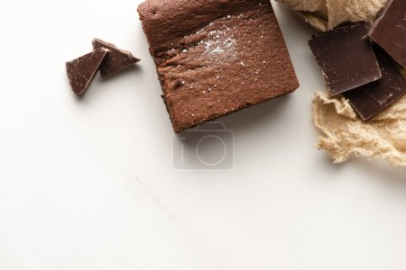 Photo for Top view of delicious brownie piece with chocolate on white background - Royalty Free Image