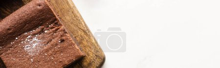 Photo for Top view of delicious brownie piece on wooden cutting board on white background, panoramic shot - Royalty Free Image