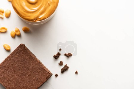 Photo for Top view of delicious brownie piece with peanut butter and nuts on white background - Royalty Free Image