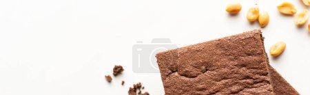 Draufsicht auf köstliche Brownie-Stücke und Erdnüsse auf weißem Hintergrund, Panoramaaufnahme