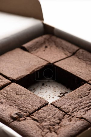 close up view of delicious brownie pieces in cardboard box on white background