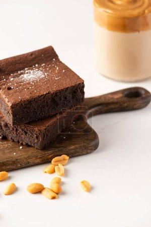 selektiver Fokus von leckeren Brownie-Stücken auf Holzschneidebrett mit Erdnüssen auf weißem Hintergrund