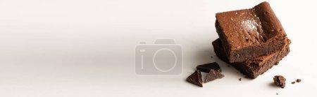 Photo pour Délicieux morceaux de brownie avec du chocolat sur fond blanc, panoramique - image libre de droit