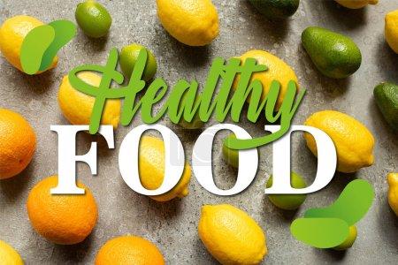 plat posé avec des chaux colorées, des oranges, des avocats et des citrons sur la surface en béton gris, illustration d'aliments sains