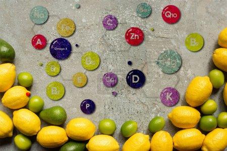 Photo pour Vue de dessus de l'avocat coloré, citrons verts et citrons sur la surface en béton gris, illustration de vitamines - image libre de droit