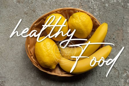 Photo for Top view of colorful bananas and lemons in wicker basket on grey concrete surface, healthy food illustration - Royalty Free Image