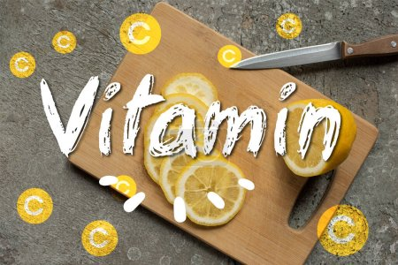 Photo for Top view of sliced lemon on wooden cutting board with knife on grey concrete surface, vitamin illustration - Royalty Free Image