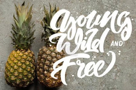 Photo for Top view of ripe pineapples on grey concrete surface with young, wild and free illustration - Royalty Free Image