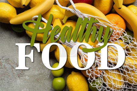 top view of colorful fruits and string bag on grey concrete surface, healthy food illustration