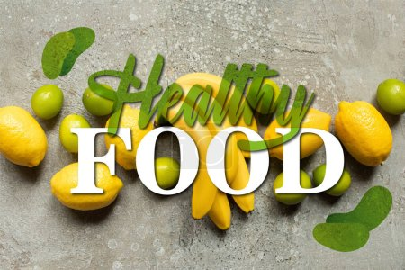 top view of colorful bananas, limes and lemons on grey concrete surface, healthy food illustration