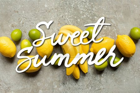 top view of colorful bananas, limes and lemons on grey concrete surface, sweet summer illustration