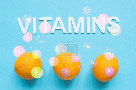Foto de Vista superior de naranjas maduras e ilustración de vitaminas sobre fondo azul - Imagen libre de derechos